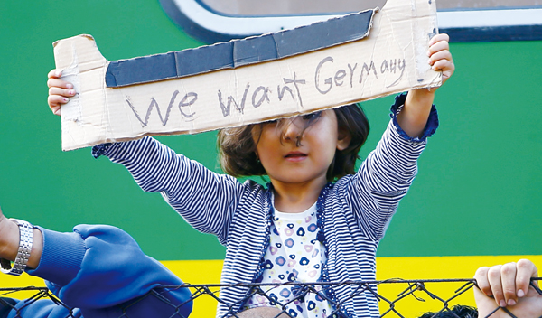 A young migrant girl holds up a sign during a protest in front of a train at Bicske railway station, Hungary, September 4, 2015. Hundreds of migrants, many of them refugees from the Syrian war, woke after a night spent on a packed train stranded at a railway station west of Budapest, refusing to go to a nearby camp to process asylum seekers. The train had left Budapest on Thursday morning after a two-day standoff at the city's main railway station as police barred entry to some 2,000 migrants. Hungary says they must be registered, as per European Union rules, but many refuse, fearing they will be sent back to Hungary if caught later in western and northern Europe. REUTERS/Leonhard Foeger TPX IMAGES OF THE DAY